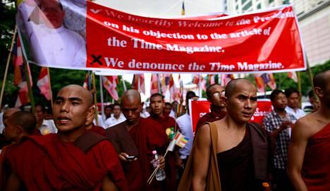 """Buddhalaiset munkit osoittivat mieltä Time-lehteä vastaan Myanmarin pääkaupungissa Yangonissa 30. kesäkuuta. Lehti nimitti kannessaan radikaalia buddhalaisjohtajaa Ashin Wirathua """"buddhalaisen terrorismin kasvoiksi""""."""