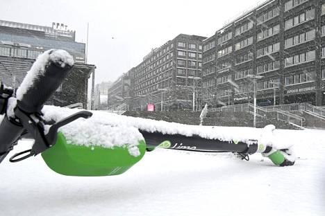 Sähköpotkulauta lumisateessa Kampissa torstaina.
