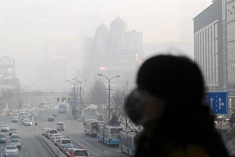 Nainen käytti kasvosuojusta savusumuisessa Pekingissä 16. tammikuuta.