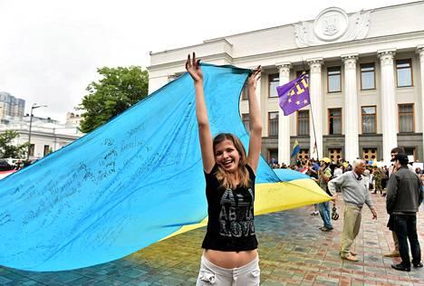 Tyttö ja muut itäisestä Ukrainasta lähteneet pakolaiset osoittivat mieltään Kiovan parlamenttitalon edustalla.