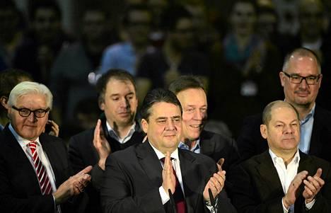 Frank-Walter Steinmeier (vas.) ja puoluetoverit taputtivat Saksan sosiaalidemokraattien hallitusyhteistyöpäätökselle yhdessä puoluejohtaja Sigmar Gabrielin (keskellä) kanssa.