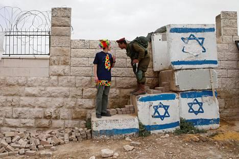 Juutalaisten purim-juhlaan osallistuva mies keskustelee israelilaissotilaan kanssa Hebronissa sunnuntaina.