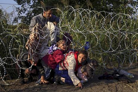 Syyrialaiset pakolaiset alittivat piikkilanka-aitaa Serbian ja Unkarin välisellä rajalla viime elokuussa. Unkari on yksi on maista, jotka saattavat karsastaa EU-maille FT:n mukaan kaavailtua korkeaa maksua, joilla voisi välttää kiintiöiden mukaisten pakolaisten vastaanottamisen.