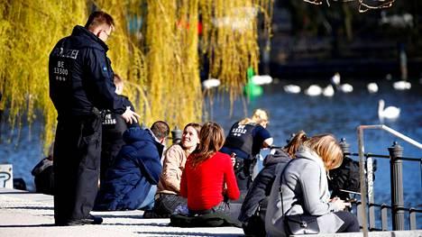 Poliisit partioivat puistossa Berliinissä 4. huhtikuuta muistuttaen ihmisiä suosituksesta säilyttää vähintään puolentoista metrin etäisyys.