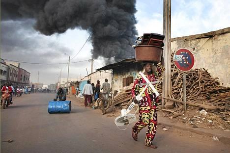 Kauppiaat kantoivat tuotteitaan turvaan tulipalon tieltä Bamakossa, Malin pääkaupungissa, lauantaina.