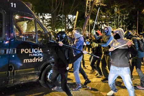 Naamioituneet mielenosoittajat hyökkäsivät poliisiauton kimppuun Madridissa lauantai-iltana.