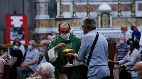 Katolinen pappi Mario Carminati kiertää jakamassa ehtoollista erityisjärjestelyin pidetyssä jumalanpalveluksessa. Seriaten pikkukaupunki sijaitsee koronaviruksen pahoin runtelemalla alueella Lombardiassa.
