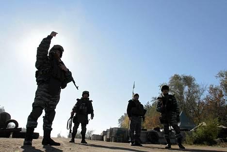 Ukrainan sisäministeriön erikoisjoukkojen univormuihin pukeutuneet poliisit vartioivat tarkastuspisteellä Luganskissa lauantaina.