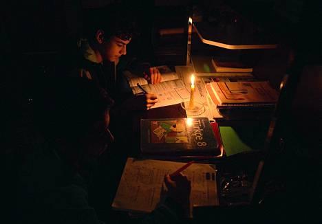 Opiskelija teki koulutöitään kynttilänvalossa Diarbakirin kaupungissa sähkökatkosten piemennettyä laajoja alueita tiistaina.