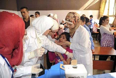 Syyrialaiset terveystyöntekijät antoivat koulutytölle poliorokotetta Damaskoksessa lokakuussa. Polio on alkanut yleistyä erityisesti nuorten lasten keskuudessa.