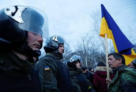 Mielenosoittaja piteli Ukrainan lippua uhmatessaan poliiseja Novi Sanzharyssa torstaina.