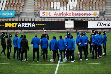 Päävalmentaja Markku Kanerva ja pelaajat neuvonpidossa viheriöllä.