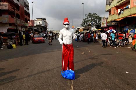 Valkoiseksi värjätty, tonttulakkiin pukeutunut mies poseerasi keskellä katua norsunluurannikkolaisessa Adjamessa jouluaattona.