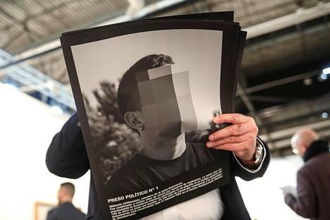 """Näyttelyvieras selasi esitettä Santiago Sierran poistetusta taideteoksesta nimeltä """"Poliittiset vangit nyky-Espanjassa"""" Arco-taidemessuilla Madridissa helmikuussa."""