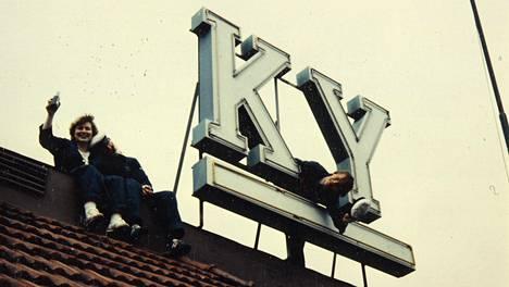 Kauppatieteen opiskelijoita KY-talon katolla 1960- tai 1970-luvulla. Ikoniset mainoskirjaimet uusittiin vuonna 2018 vanhojen valoputkien rikkoutumisen takia.