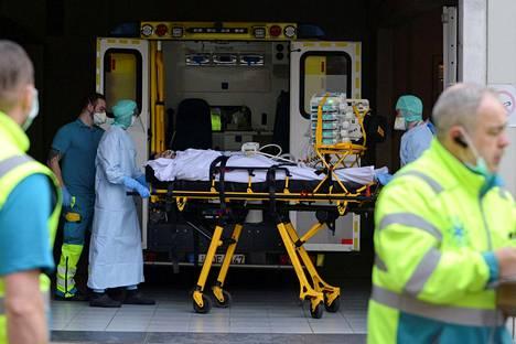Belgian Liègessä sijaitsevan sairaalan väki siirtämässä koronavirukseen sairastunutta potilasta perjantaina.