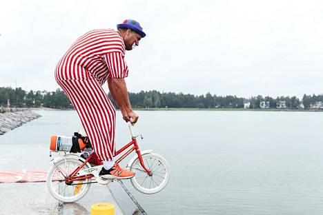 Werneri Wetelä polkee veteen. Pyörään kiinnitetty mehukanisteri estää pyörän uppoamisen.