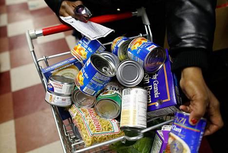 Nainen keräsi ruokaa kärryihinsä avustuskeskuksessa Harlemissa New Yorkissa.