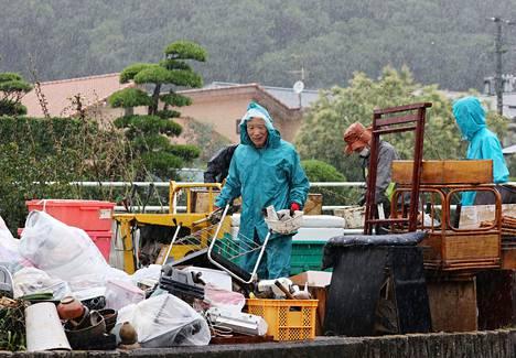 Asukkaat keräämässä tuhoutuneita tavaroitaan roskapusseihin Ashikitan alueella Kumamoton prefektuurissa torstaina.