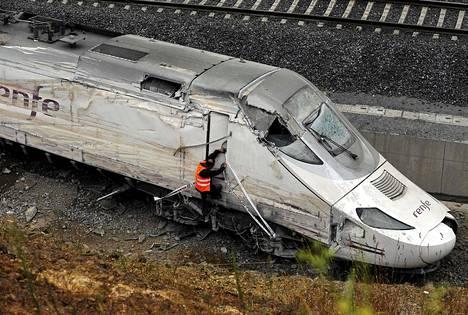 Virkailija tutkii onnettomuusjunan veturia.