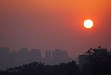 Aurinko laskee maastopalojen levittämän savun takaa Sydneyssä maanantaina.