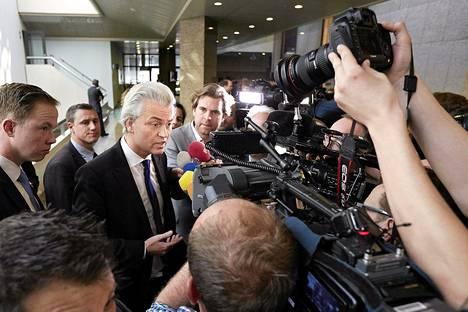 Geert Wilders selitti puheitaan medialle torstaina parlamentin edessä.