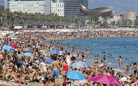 Ihmiset täyttivät hiekkarannan Barcelonassa elokuussa 2015. Taustalla arkkitehti Frank Gehryn suunnittelema kullanvärinen kalaveistos, joka valmistui useiden hiekkarantojen tavoin kesän 1992 olympialaisiin.