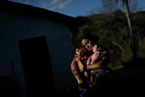 Brasilialainen Raquel Barbosa sylissään kymmenkuiset kaksoistyttäret Heloa ja Heloisa. Tytöt sairastavat pienipäisyyttä, jonka syyksi epäillään Latinalaisessa Amerikassa yleistynyttä hyttysten levittämää zikavirusta.
