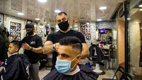 Mustafa Rashid (vas.) leikkaa  Jonas Kareemin hiuksia  parturi-kampaamo Jaffissa.