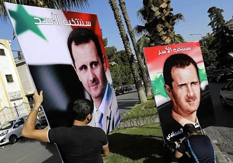 Syyrialaiset miehet kantoivat presidentti Bashar al-Assadin vaalijulisteita Damaskoksessa sunnuntaina.