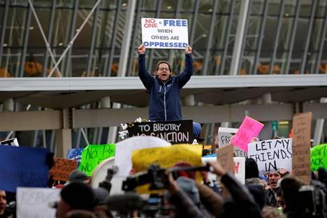 Väkijoukko osoitti mieltään presidentti Donald Trumpin uusia maahantulokieltoja vastaan John F. Kennedyn lentokentällä New Yorkissa lauantaina.