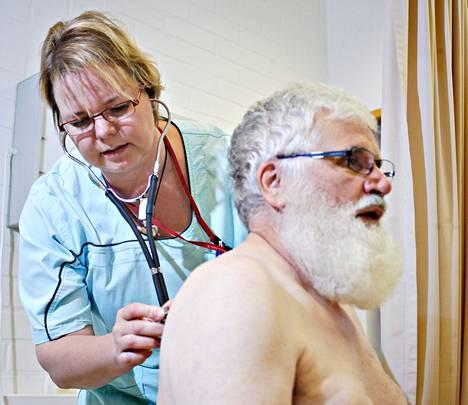 Sairaanhoitaja Mari Ruttonen tutkii muun muassa flunssapotilaita vastaanotollaan Hankasalmen terveysasemalla. Osmo Vilokkinen kävi hoidettavana hengenahdistuksen vuoksi.
