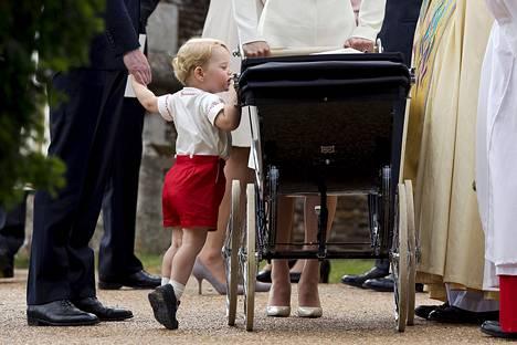 Britannian prinssi George kurkisti vaunuissa lepäävää pikkusisartaan prinsessa Charlottea kastetilaisuuden jälkeen.