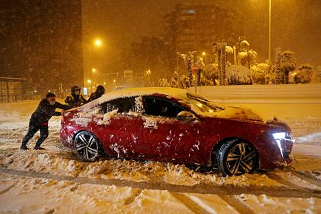 The townspeople pushed a car stuck in the snow in a snowfall in Madrid on Friday.