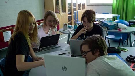 Helsingin kielilukiossa opiskelevat Edith Turtola (edessä oikealla), Emili Karmanov (edessä vasemmalla), Daria Kaukiainen (takana vasemmalla) ja Ida Nordgren suosivat sähköisiä oppimateriaaleja perinteisten kirjojen sijaan.