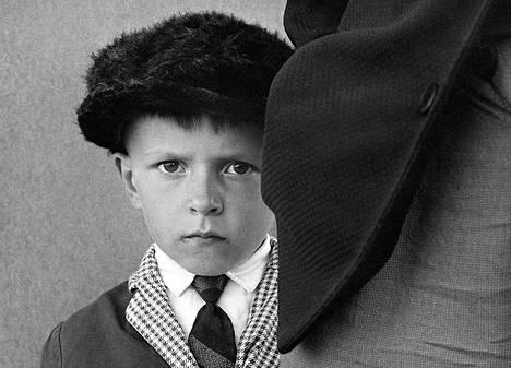 Ismo Höltön valokuva miehen takinliepeen takaa katsovasta pojasta.