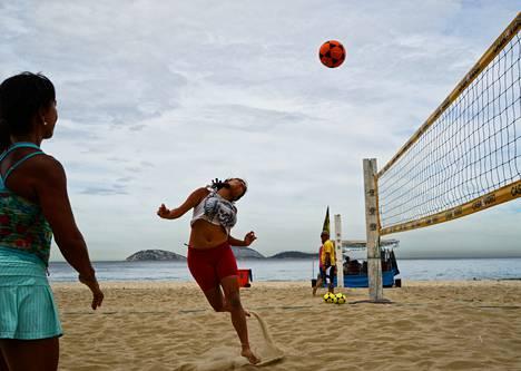 Luiza Sampaio pukkaa pallon yli verkon. Vera Lucia Montoto katsoo vierestä.