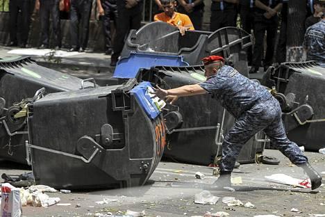 Poliisi siirsi mielenosoittajien barrikaadeiksi asetettamia roskalaatikoita Jerevanissa Armeniassa maanantaina.