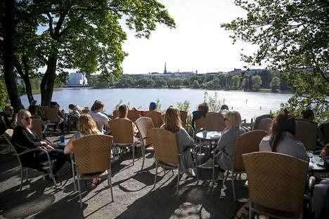 Vuosi sitten aurinkoinen sää helli Helsinkiä. Kuvassa ihmisiä Linnulaulun kahvilassa 22.5.2016.
