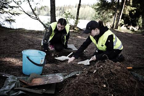 Taika-Tuuli Kaivo (vas) ja Emmi Karvinen kaivavat kuoppaa Bodomin järven arkeologisilla kaivauksilla.