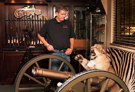 Asekauppias Rich Wyatt esittelee myymälässään puumaa, jonka hän ampui pistoolilla.