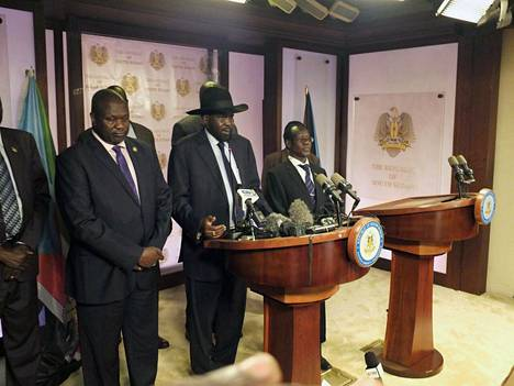 Etelä-Sudanin presidentti Salva Kiir (kesk.), varapresidentti Rieka Machar (vas.) ja joukko valtion edustajia tiedotustilaisuudessa Jubassa perjantaina.