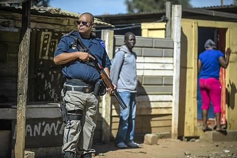 Poliisit valvoivat kun ulkomaalaistaustaiset myyjät tyhjensivät kauppojaan levottomuuksien varalta Johannesburgin lähistöllä torstaina.