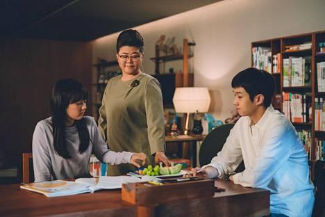 Työttömät Kimin perheen nuoret saavat töitä varakkaan perheen kodista. Kuvassa vasemmalta tytär Ki-jung (Park So-dam), kodinhoitaja Moon-gwang (Lee Jung-eun) sekä poika Ki-woo (Choi Woo-shik).