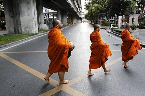 Buddalaismunkit ylittämässä tietä aamuvarhaisellla Bankokissa, Thaimaassa.