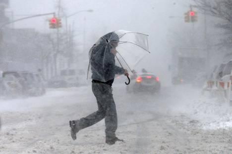 Sateenvarjolla suojautunut mies ylittää sohjoista katua New Yorkin Manhattanilla torstaina, kun Yhdysvaltain itärannikko joutui rajun lumimyräkän kouriin.
