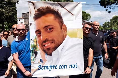 """Ihmiset kantoivat Mario Cerciello Regan hautajaisten yhteydessä viime heinäkuussa tämän kuvaa, johon oli kirjoitettu """"ikuisesti kanssamme""""."""