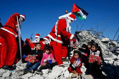 Joulupukki jakoi lahjoja tuhoutuneen talon raunioilla al-Khaderin kylässä lähellä Betlehemiä Palestiinan Länsirannalla aatonaattona maanantaina.