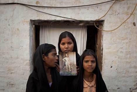 Asia Bibin tyttäret esittelivät jumalanpilkasta kuolemantuomion saaneen äitinsä kuvaa Sheikhupurassa lokakuussa 2010.