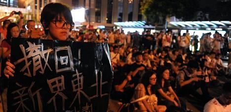 Mielenosoittaja kantoi plakaattia tiistain mielenosoituksessa.